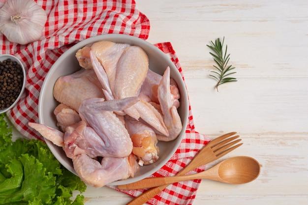 Rauwe kippenvleugels op het witte houten oppervlak.