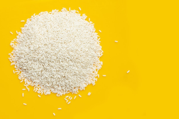 Rauwe kleverige rijst op gele achtergrond.