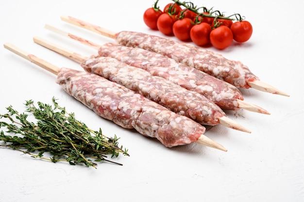 Rauwe kofta vlees kebab worstjes set, met ingrediënten van de grill, op witte stenen tafel achtergrond