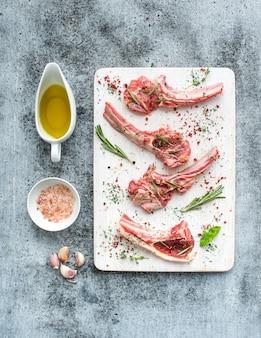 Rauwe lamskoteletjes. lamsrack met knoflook, rozemarijn en specerijen op zwart wit houten bord, olie in een schotel, zout over grijze grunge oppervlak.