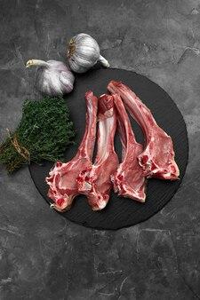 Rauwe lamskoteletten met knoflook, kruiden op zwarte keramische plaat over witte steengrijze tafel. bovenaanzicht. met kopie ruimte.