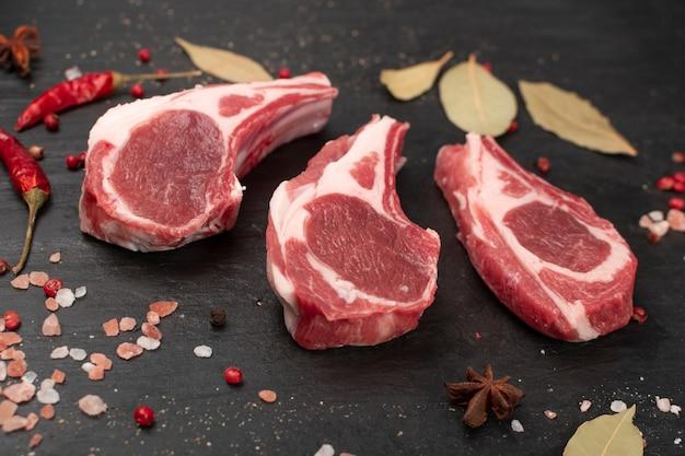 Rauwe lamskoteletten of schapenvlees met zout en kruiden. de verse kotelet van schapenribben op beenclose-up