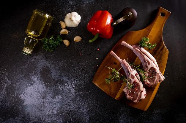 Rauwe lamsribbetjes snijplank met kruiden en geroosterde groenten