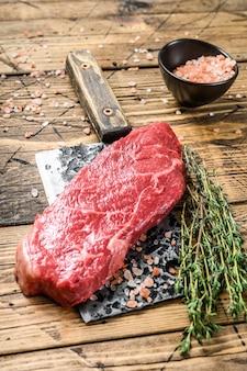 Rauwe lendenstuk biefstuk op een hakmes, gemarmerd rundvlees. houten achtergrond. bovenaanzicht.