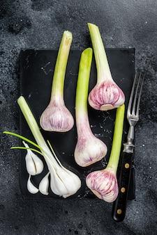 Rauwe lente jonge knoflookbollen en kruidnagel op marmeren bord