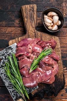 Rauwe lever kip slachtafvallen vlees op een houten snijplank met slager hakmes. donkere houten achtergrond. bovenaanzicht.