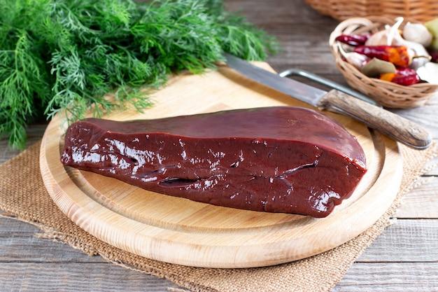 Rauwe lever klaar om te koken op een houten bord in de rustieke keuken, kookproces. concept van gezond eten