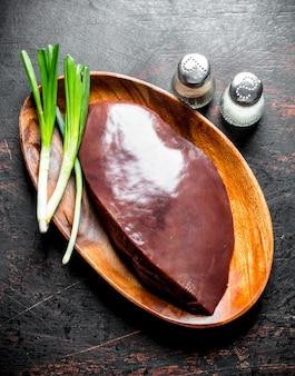 Rauwe lever op een houten plaat met groene uien. op donkere rustieke ondergrond