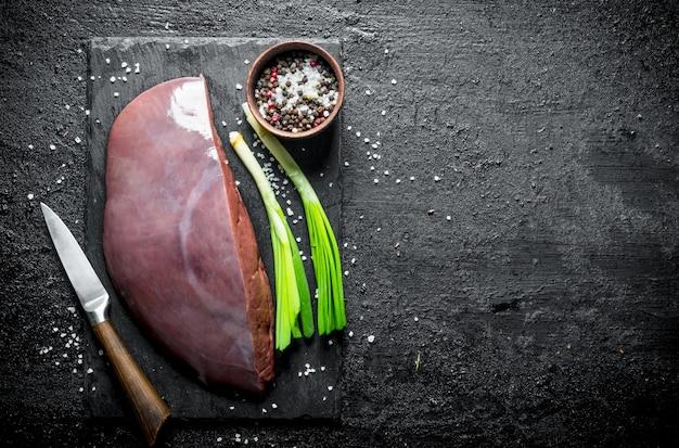 Rauwe lever op stenen bord met groene uien en kruiden op zwarte rustieke tafel