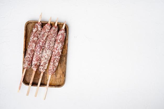 Rauwe lula kebab op spiesjes set, op witte stenen tafel achtergrond, bovenaanzicht plat lag, met kopieerruimte voor tekst