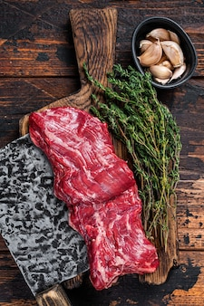 Rauwe machete rok biefstuk op slager bord met hakmes. donkere houten achtergrond. bovenaanzicht.