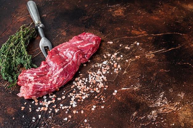 Rauwe machete rok biefstuk op vleesvork. donkere achtergrond. bovenaanzicht. ruimte kopiëren.
