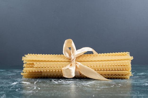 Rauwe mafaldine pasta vastgebonden met lint op blauwe tafel.