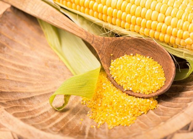 Rauwe maïs met groene bladeren op een witte achtergrond.