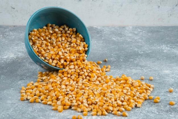 Rauwe maïskorrels uit kom op marmeren oppervlak.