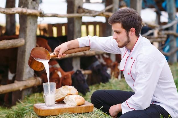 Rauwe melk, een man giet melk tegen de achtergrond van koeien.