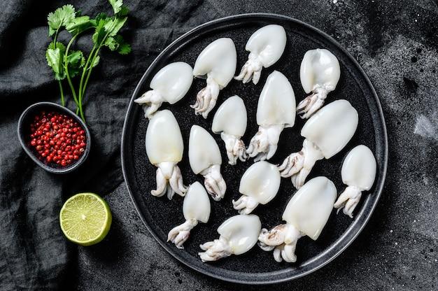 Rauwe mini-inktvis met rozemarijn en peterselie op een bord