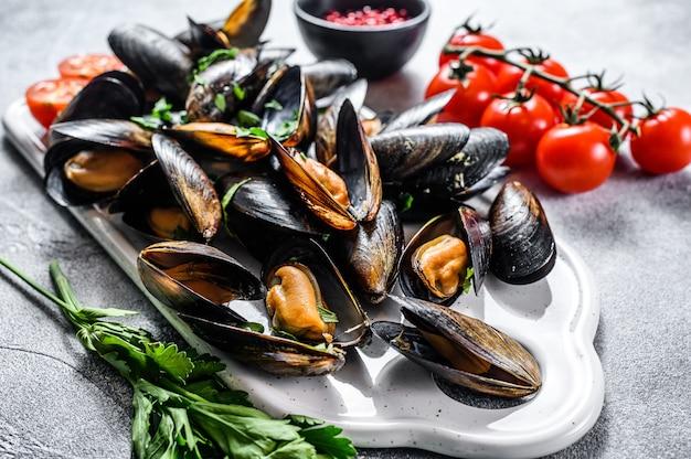 Rauwe mosselen in schelpen op een snijplank. het concept van het koken van zeevruchten in tomatensaus met peterselie. grijze achtergrond. bovenaanzicht