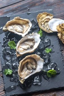 Rauwe oesters op de zwarte stenen bord