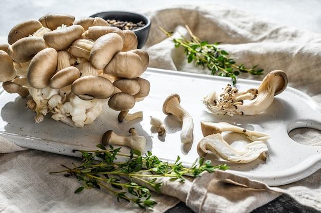 Rauwe oesterzwammen op een wit snijplank met tijm. grijze achtergrond. bovenaanzicht