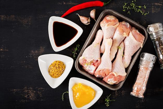Rauwe ongekookt kippenpoten en kruiden op donkere tafel