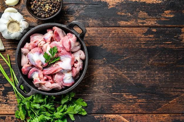 Rauwe ongekookte kippenmaagjes, maag in een pan. donkere houten achtergrond. bovenaanzicht. kopieer ruimte.