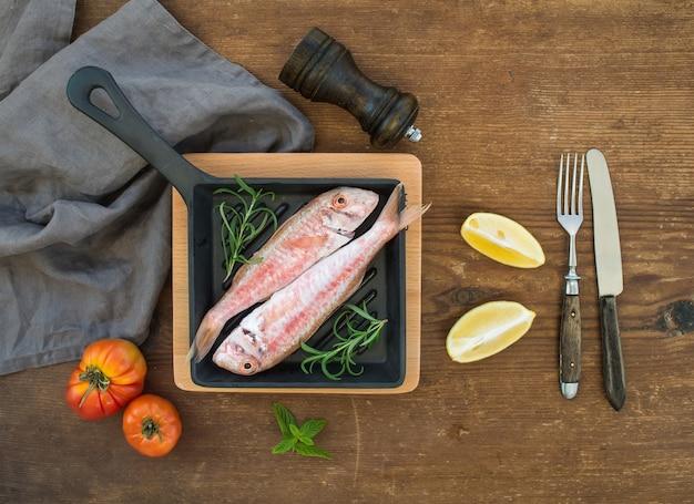 Rauwe ongekookte rode mul vis in een pan met rozemarijn, citroen en knoflook