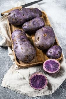 Rauwe paarse aardappelen op een snijplank. grijze achtergrond. bovenaanzicht