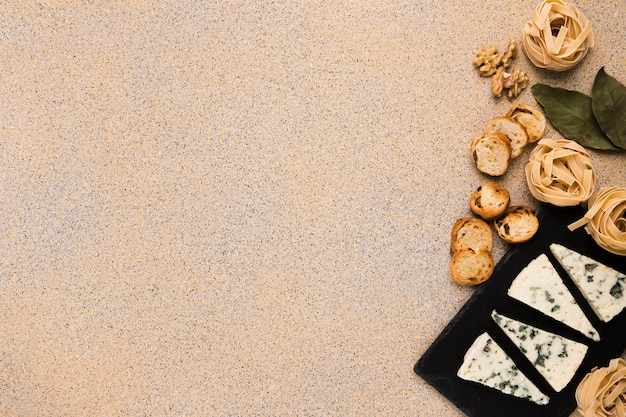 Rauwe pasta ballen; sneetjes brood; walnoot en laurierblaadjes met gorgonzola-kaas op leisteen aan de rechterkant van de achtergrond