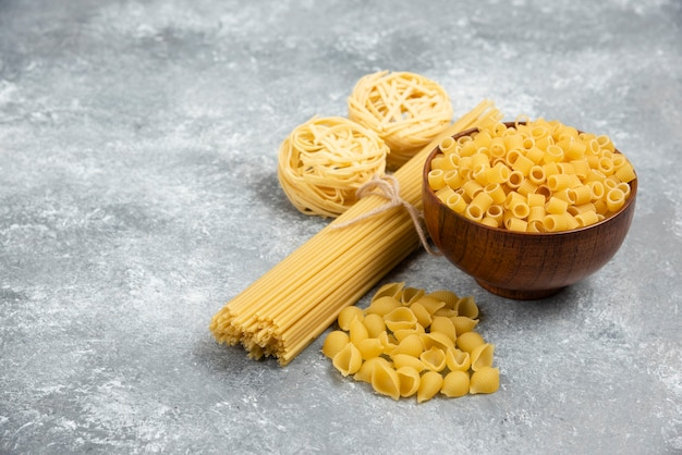 Rauwe pasta en spaghetti-variëteiten op marmeren tafel.
