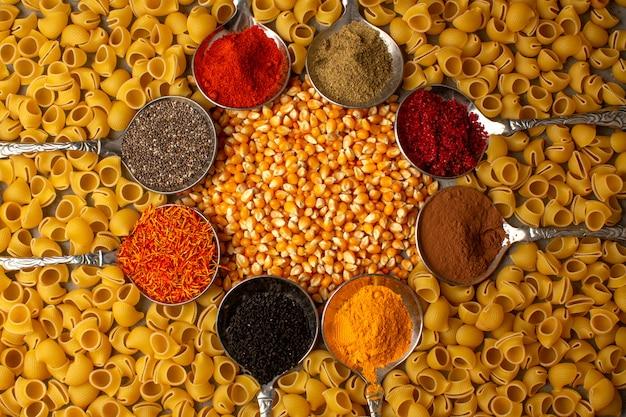 Rauwe pasta geel samen met kleurrijke kruiden in zilveren lepels