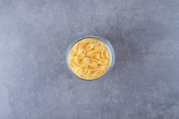 Rauwe pasta in glas op stenen achtergrond. Gratis Foto