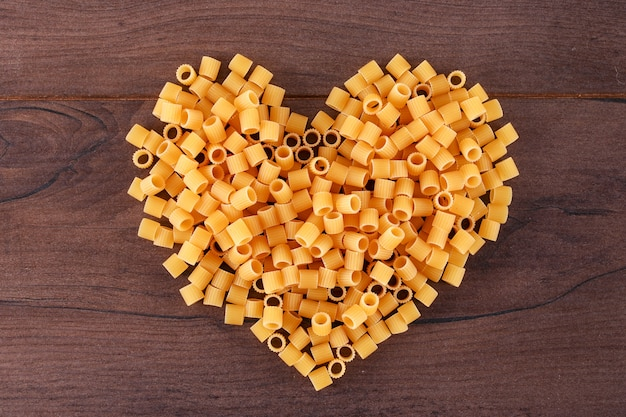 Rauwe pasta in hartvorm bovenaanzicht op houten oppervlak