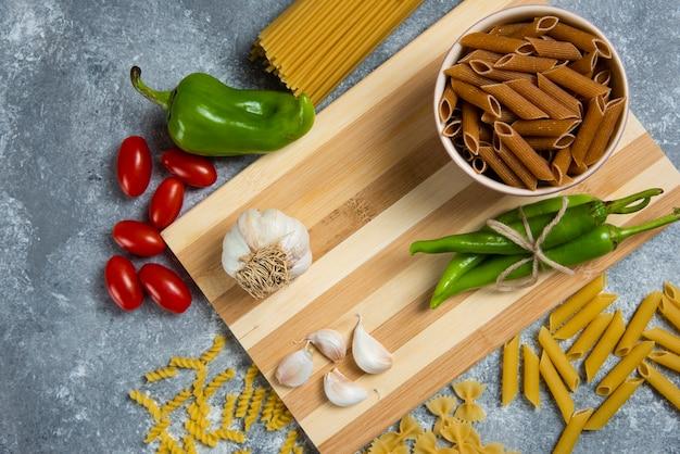 Rauwe pasta met groenten op een houten bord.