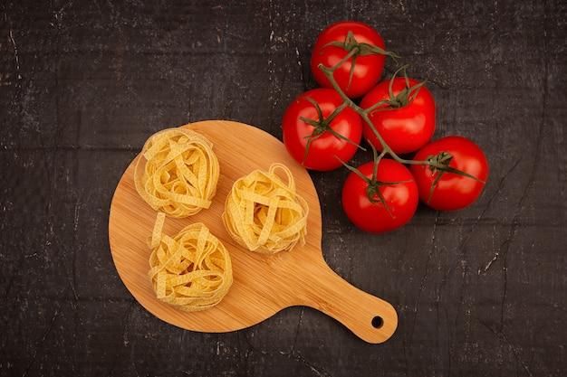 Rauwe pasta met tomaten op een houten snijplank