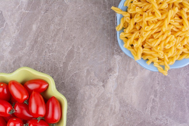 Rauwe pasta's in een kopje met rode kerstomaatjes rond