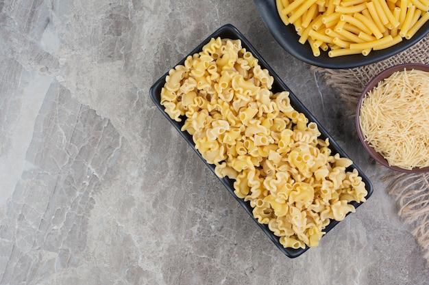 Rauwe pasta's in zwarte keramische schotel op het marmer.