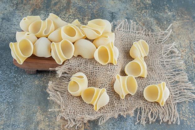 Rauwe pasta's op onderzetter, op het marmeren oppervlak.