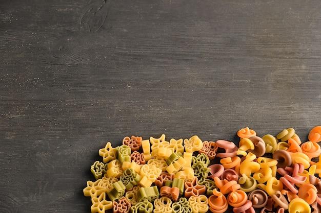 Rauwe pasta van verschillende kleuren en soorten op een houten donkere tafeltafel