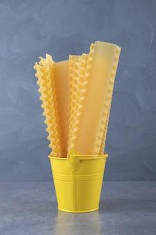 Rauwe pasta voor het bakken van lasagne in gele emmer.