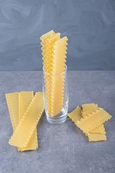 Rauwe pasta voor het bakken van lasagne op stenen achtergrond.