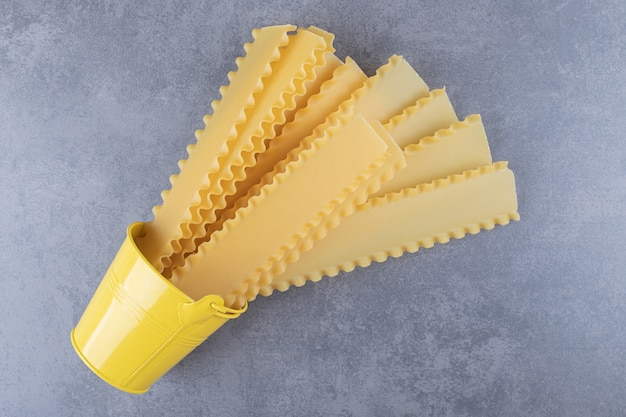 Rauwe pasta voor het bakken van lasagne uit gele emmer.