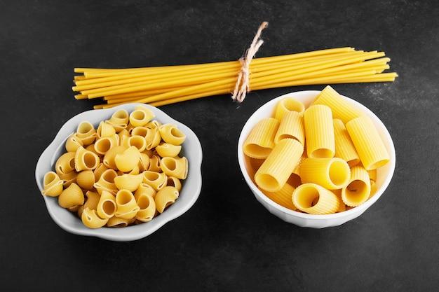 Rauwe pastasoorten in keramische kopjes.