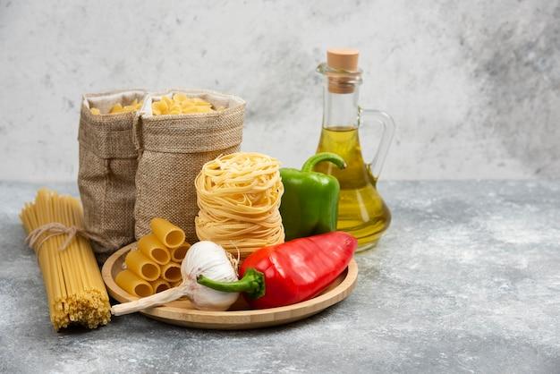 Rauwe pastasoorten met knoflook, chilipepers en olijfolie.