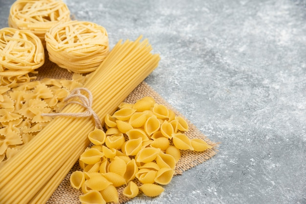 Rauwe pastasoorten op een stuk jute.