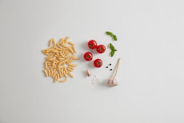 Rauwe penne-eierpasta met verse biologische ingrediënten cherrytomaatjes, knoflook, basilicum, zeezout, peperkorrels. gezond voedsel en voedingsconcept. producten voor het koken van traditionele italiaanse gerechten.