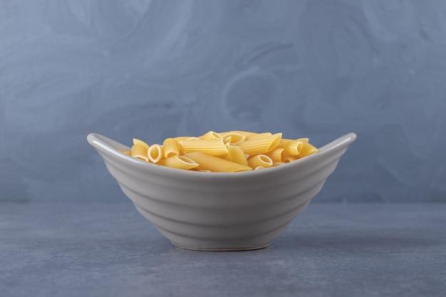 Rauwe penne pasta in keramische kom.