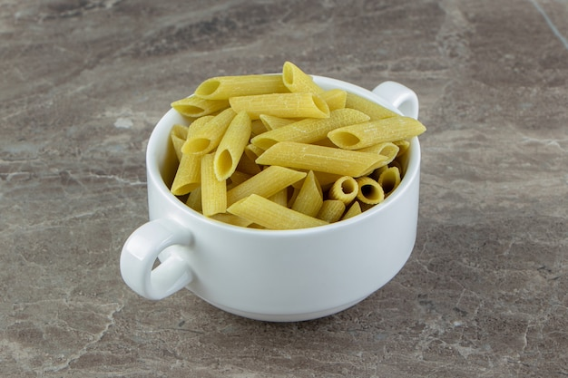 Rauwe penne pasta in witte mok