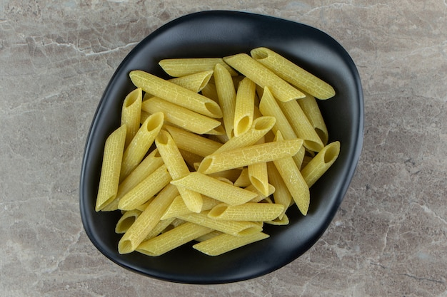 Rauwe penne pasta in zwarte kom
