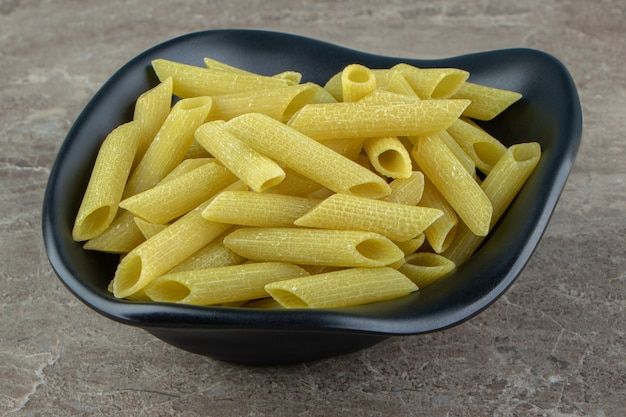 Rauwe penne pasta in zwarte kom.